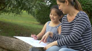 Happy Asian Daughter drawing picture with mother together in the park