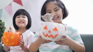 Slow motion 4K Happy Asian girl playing hide and seek with little kitten inside pumpkin bucket, Happy Halloween