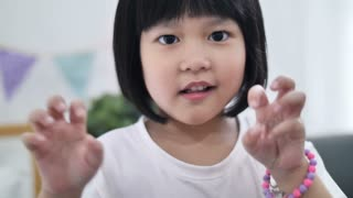 Slow motion 4K Happy little Asian girl who pretend to be monster making a scary face
