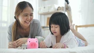 Slow motion 4K Lovely little Asian girl and mother putting money in piggy bank for saving