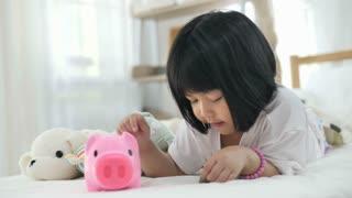 Slow motion 4K Lovely little Asian girl putting money in piggy bank for saving
