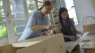 Slow motion Asian girl helping her mother assembling new DIY furniture at home, close up shot