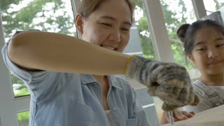 Slow motion Asian girl helping her mother assembling new DIY furniture at home, Pan shot