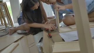 Slow motion Asian girl helping her mother assembling new DIY furniture at home, Tilt up shot
