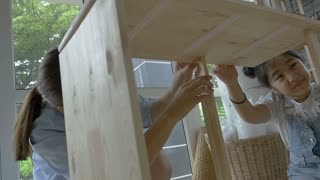 Slow motion Asian girl helping her mother assembling new DIY furniture at home