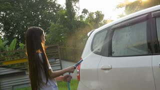 Slow motion Happy Asian girl washing car on water splashing and sunlight at home