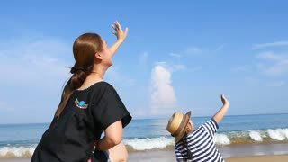 Slow motion Happy Asian woman and daughter waving to the plane on the sky, Tilt up shot