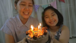 Slow motion happy moment of Asian daughter and mother blowing birthday candles, Looking camera shot