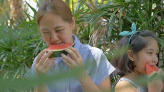 Slow motion of Asian child girl and mother eating delicious water melon