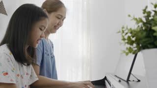 Slow motion of Asian girl playing piano with her mother, Zoom out