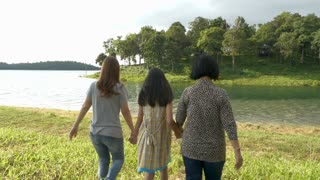 Slow motion of Happy Asian girl walking with her family in the field beside the lake, Multi generations