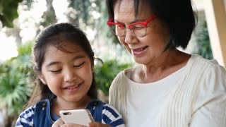Slow motion of little Asian girl using smart phone with her grandmother
