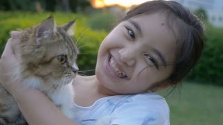 Slow motion of lovely Asian girl plays with her Persian cat in the park