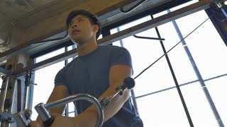 Slow motion of young Asian man exercising in the fitness gym, Pan shot