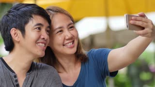 Young Asian couple in love makes selfie with smartphone