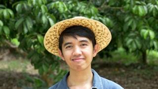 Young Asian farmer holding rambutan on his farm in Thailand