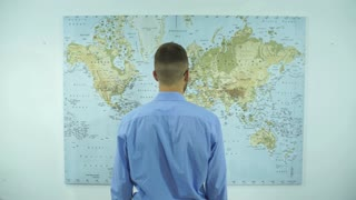 a businessman looks at a map of the world