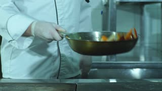 A chef flipping vegetables in a frying pan