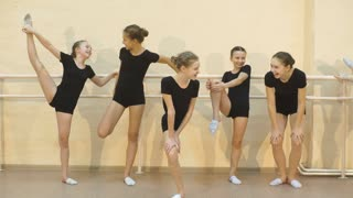 a group of girls stretching on a barre during a ballet lesson for dance class