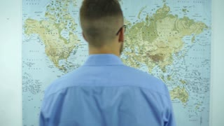 a man looks at a map of the world