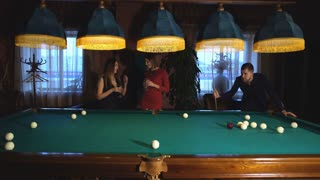 a man plays Billiards and two young beautiful women watching the game