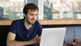a man sitting in a cafe and working at a laptop