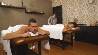 A young couple relaxes on couples massage in a Spa cente