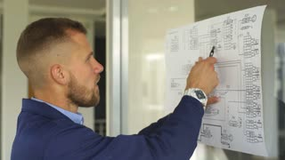 architect builder studying layout plan of the rooms, serious civil engineer working with documents on construction site