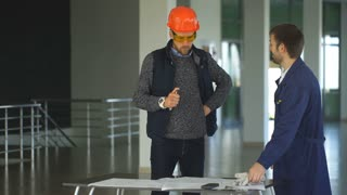 Architect or engineer working on blueprint and architecture model in hall