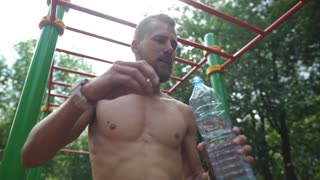 Athletic young man drinking water from a bottle