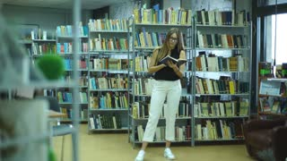 attractive student girl reading book in library