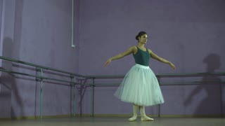 ballerina making a jump in a dance hall. She is wearing the leotard with white tutu