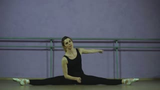 ballerina stretches in the hall