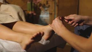 beautiful blonde girl doing foot massage. Therapeutic massage.