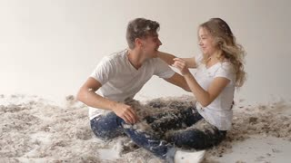 beautiful boy and girl hugging in the studio in feathers