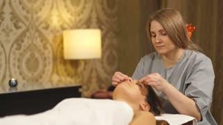 beautiful brunette doing a facial massage in a Spa center