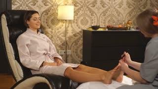 beautiful brunette girl doing foot massage. Therapeutic massage.