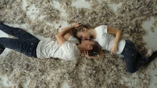 beautiful couple lying in the feathers on the floor