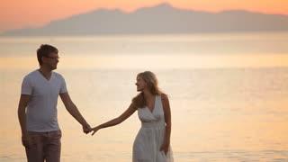 beautiful couple walking along the shore of the Aegean Sea