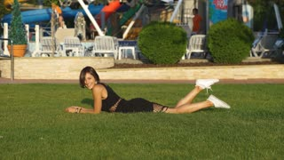beautiful girl lying on grass and laughing