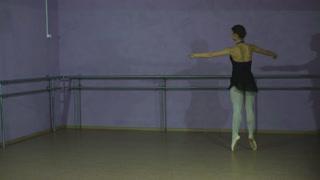 Beautiful graceful ballerine in black practice arabesque ballet position in hall