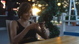 beautiful woman sitting in a cafe at sunset and typing the message