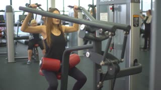 Beautiful young woman doing exercises to strengthen the shoulder simulator
