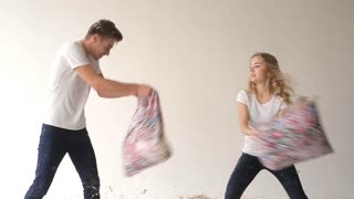 Boy and girl fighting pillows
