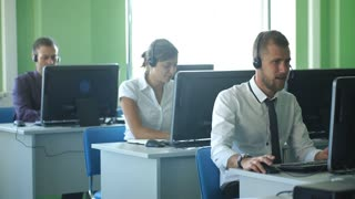 business colleagues with headsets using computers at the m dern office desk
