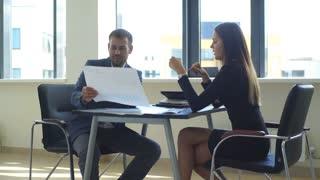 businessman shows graphics, businesswoman uses a calculator