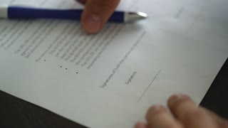 businessman signs a contract on a wooden table