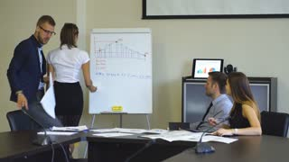 businesswoman showing graph on Board for his colleagues