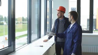 Cheerful architect and attractive foreman are looking through the window with aspirations