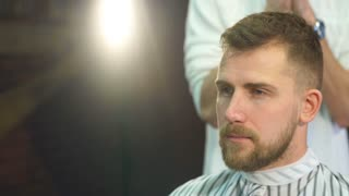 Cheerful skillful barber making a haircut with scissors to a young bearded man